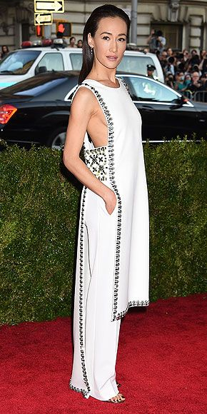 The Most Jaw-Dropping Dresses at the 2015 Met Gala | MAGGIE Q | wearing a custom Tory Burch tunic with crystal embellishments around the tunic and waist, plus matching pants and sandals by the brand.