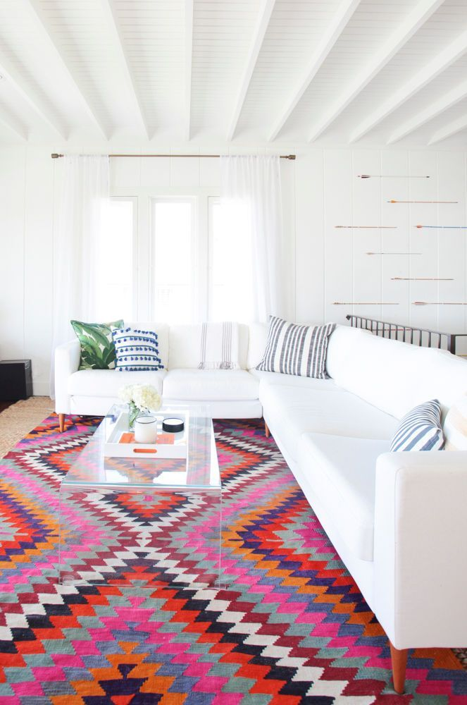 Bright living room with, exposed beams, paneled walls, large white sectional sofa, and vibrant colorful accents.