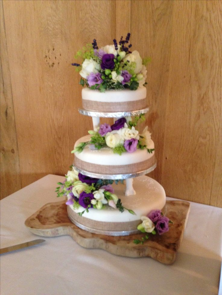 Pretty cake decoration using purple, lilac and green flowers.