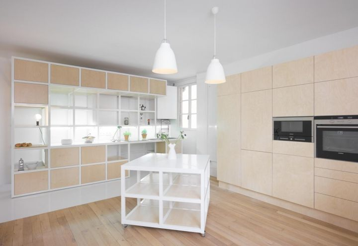 Disegnata su misura dallo studio CUT Architectures, la cucina di questo appartamento parigino è composta da una parte fissa in impiallacciato di betulla e una griglia in acciaio che integra scaffalature, armadietti e un piano di lavoro con lavello e piano cottura