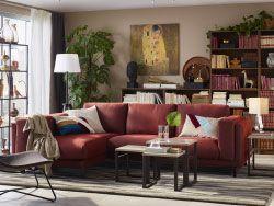 Salón de tamaño estándar con una combinación de sofá marrón rojizo para tres personas, tres mesas anidadas y un sillón marrón oscuro de fibras naturales.