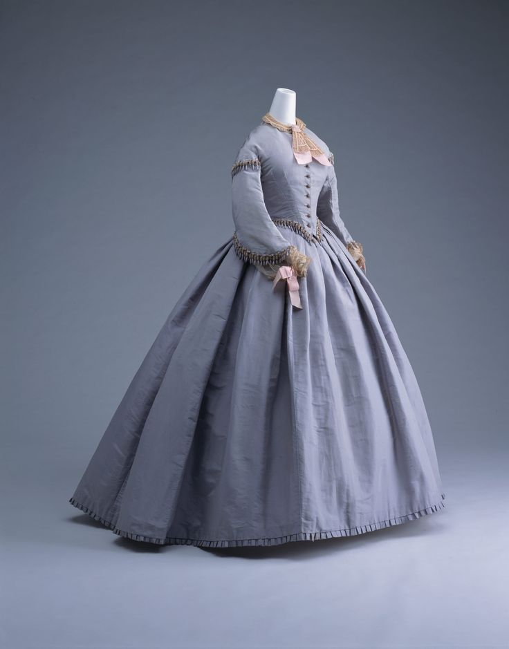 "Day Dress: ca. 1865, silk taffeta, chenille and fringe on the bodice. ""This dress is a good example of the crinoline style when skirts reached their maximum volume around 1865. Most of the volume of the skirt is concentrated on the backside. The vogue of crinoline skirts which used large amounts of silk cloth invigorated the silk industry. The improvement of weaving machines, progress in dying techniques, and introduction of the sewing machine largely revived the textile industry of that…"