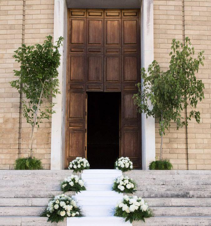 Davanti alla chiesa, alti aceri e tappeto bianco.