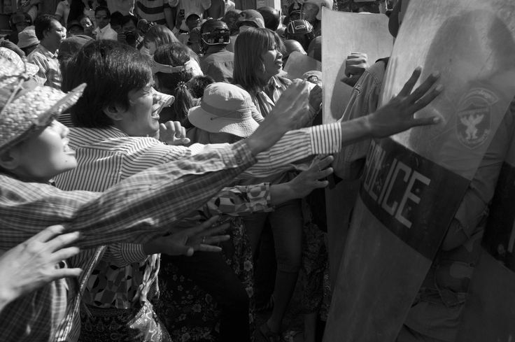 CAMBODIA. Phnom Penh. 29/11/2011: Boeung Kak lake residents trying to force a barrage of policemen blocking their way to a demonstration in front of the municipal office.