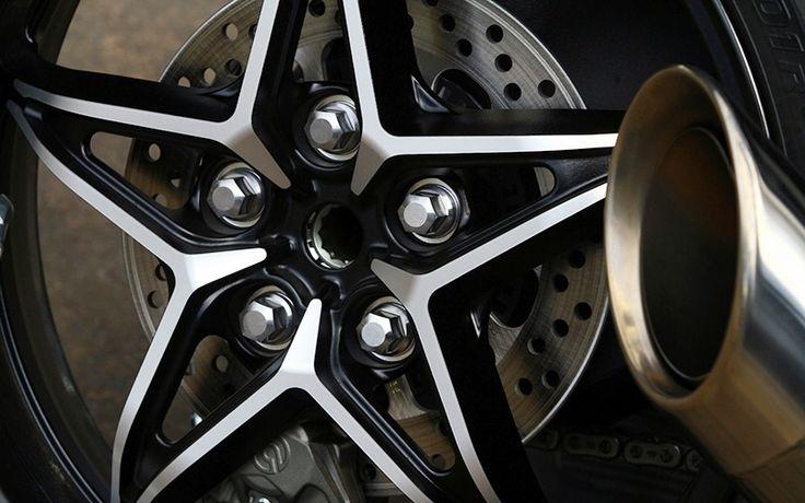 Rodas de liga leve mais parecem de um automóvel: cinco raios, cinco parafusos grandes e acabamento em dons tons