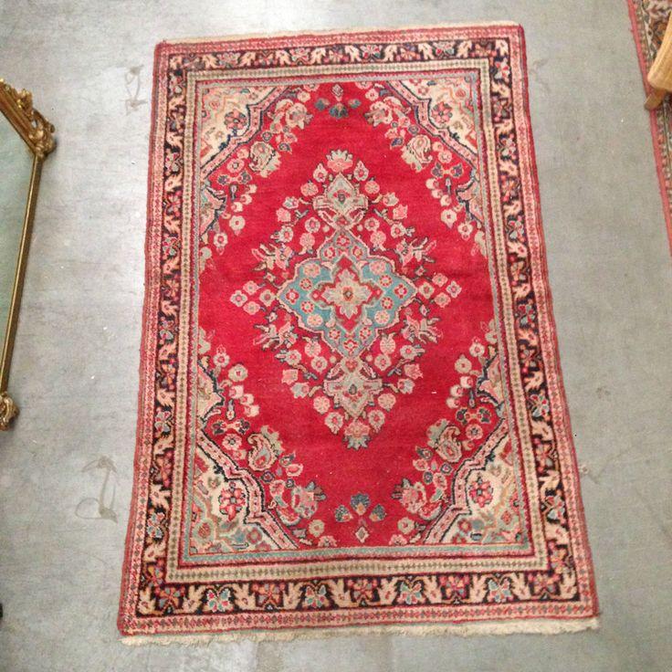 tapis d'orient model aux quatre coins , motif central floral , couleur dominante rouge . XX siècle .