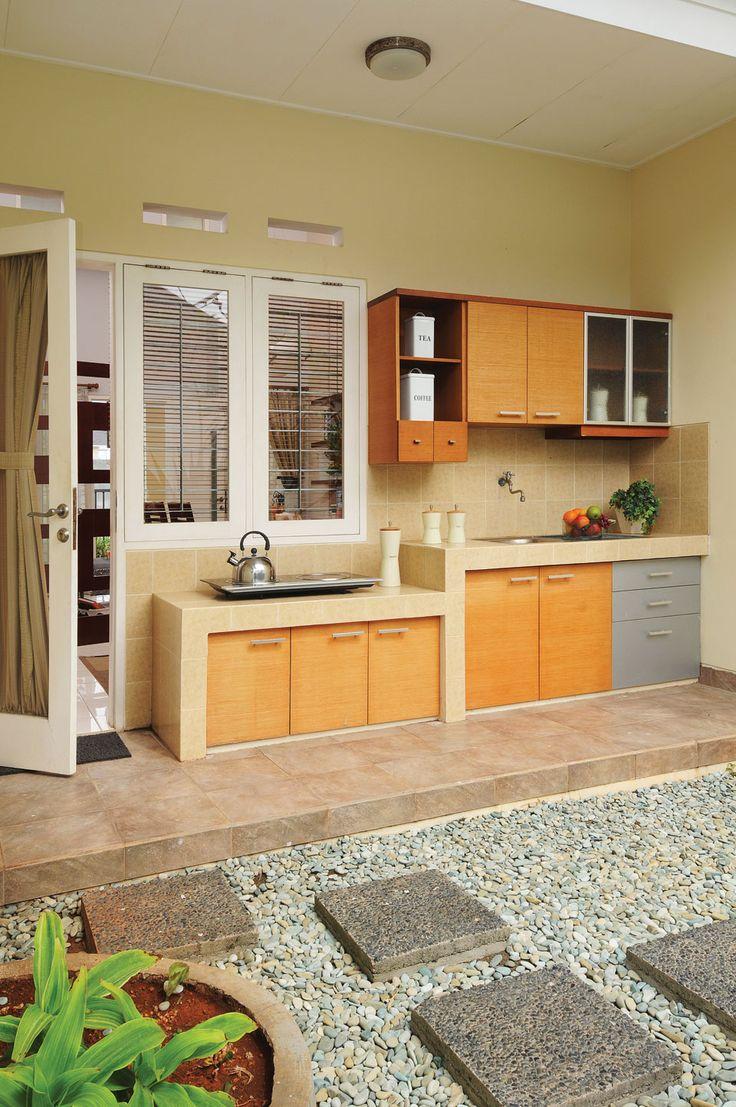 Dapur ditempatkan di area belakang agar terasa lebih luas dan terbuka. Penempatan seperti ini membuat kegiatan di dapur bisa lebih leluasa, dan tidak memerlukan cookerhood . Namun perlu diperhatikan tempias hujan dan angin.
