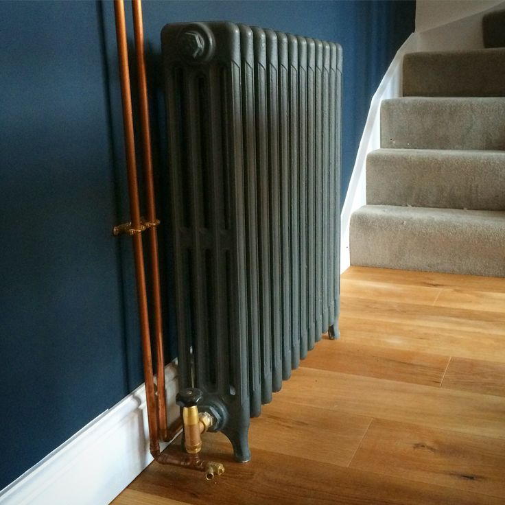 Refurbished cast iron radiator with brass valves. Copper pipes left exposed and coated. Wall painted in farrow and ball Hague blue
