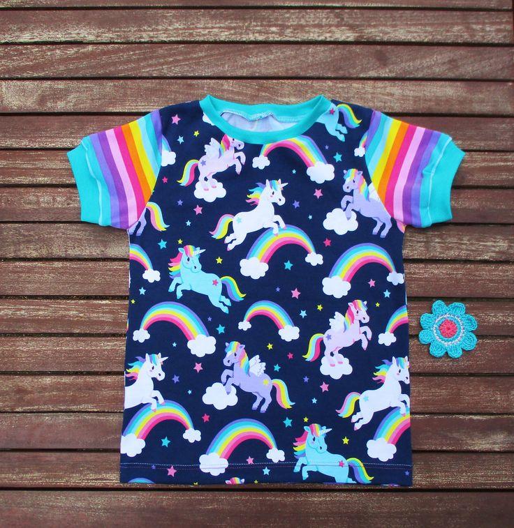 Ich habe die wunderschönen Einhörner auf Blau und die passenden Einhorn Regenbogen Ringel von Stoffwelten zu einem T-Shirt Gr.116 Weite M vernäht. Als Zugabe gibt es eine gehäkelte Blume.Die Blume auf dem Foto ist nur ein Beispiel.  Die blauen Einhörner sind die Regenbogelringel sind eine Eigenproduktion von Stoffwelten .  T-Shirt Gr.116 Weite:M ist Versandfertig.  Endlich Kinderbekleidung, die jeder Figur optimal passt (durch das eigens erschaffenes Weiten- und Längensystem von der…