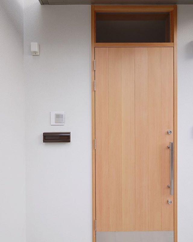 木の玄関ドアステンレスのドアハンドル玄関に明るい光が差し込むように