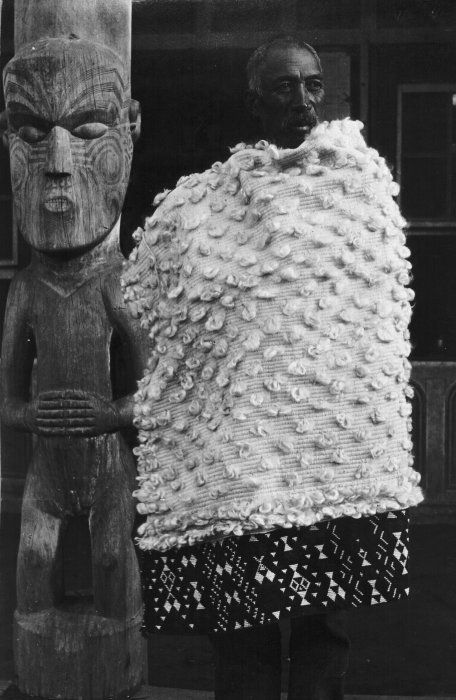 Pokiha modeling a fine flax cloak decorated with a broad taniko border along its bottom edge. Photograph taken by James Ingram McDonald at Koroniti, in 1921. Cloaks decorated with taniko on the bottom edge only are called kaitaka patea