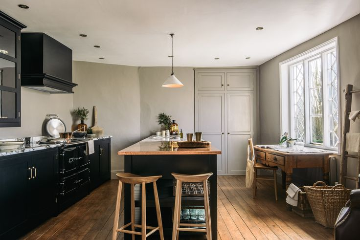 Deep grey walls, wooden floorboards, black Shaker cupboards, brass hardware and a lovely mix of kooky antiques and artisan pieces handmade by deVOL
