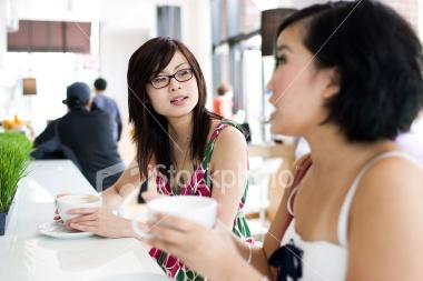 Asian Teenage Girls Having Serious Talk at Coffee Shop, Copyspace Royalty Free Stock Photo