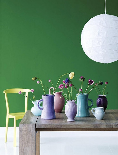 Green feature wall, with a luscious yellow chair and pops of colour from the vases on the table.