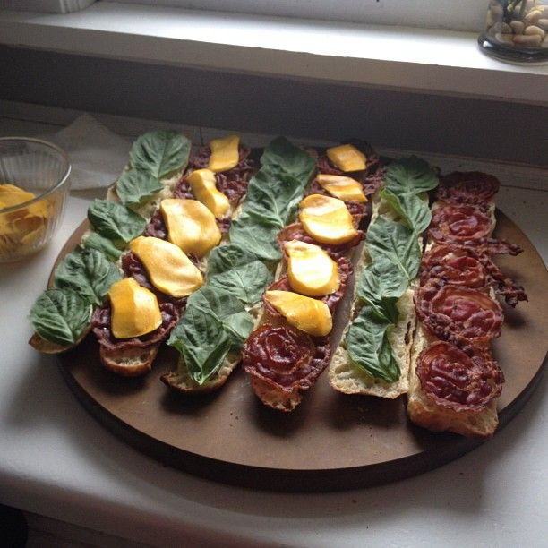 Stecca sandwiches - pancetta, basil and mago served on an Epicurean cutting board.