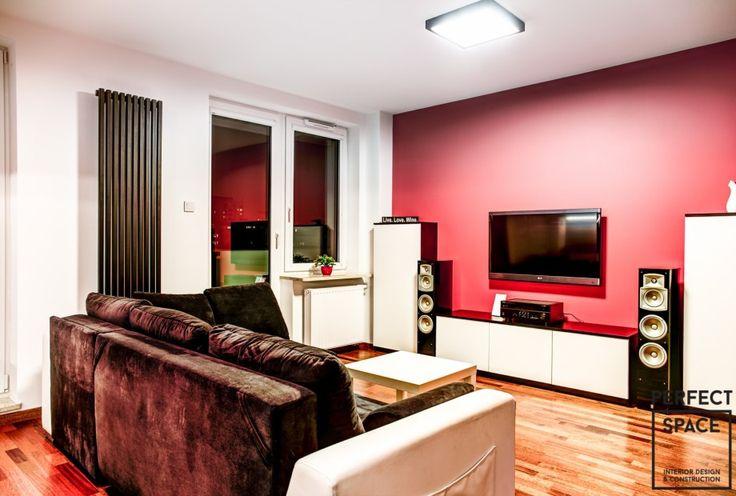 Wnętrze salonu o klasycznym układzie, gdzie wyróżnić należy nowoczesny grzejnik przymocowany wzdłuż długości, a nie szerokości okna oraz intensywną czerwoną ścianę gdzie umieszczono tv.