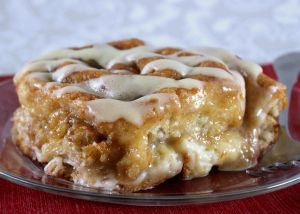 Gooey Stuffed Cinnamon Roll Bake - This easy breakfast casserole uses frozen cinnamon rolls, so it comes together in minutes! It's stuffed with a cream cheese layer and cinnamon brown sugar topping.