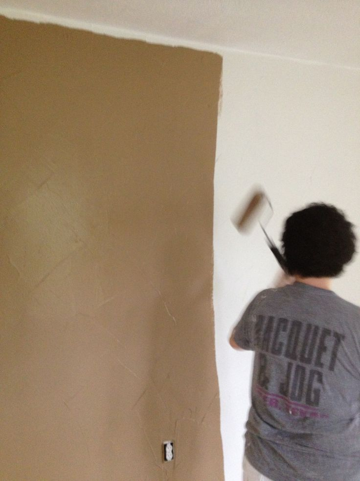 Carrie demonstrates her mad paint skills on the master bedroom accent wall.