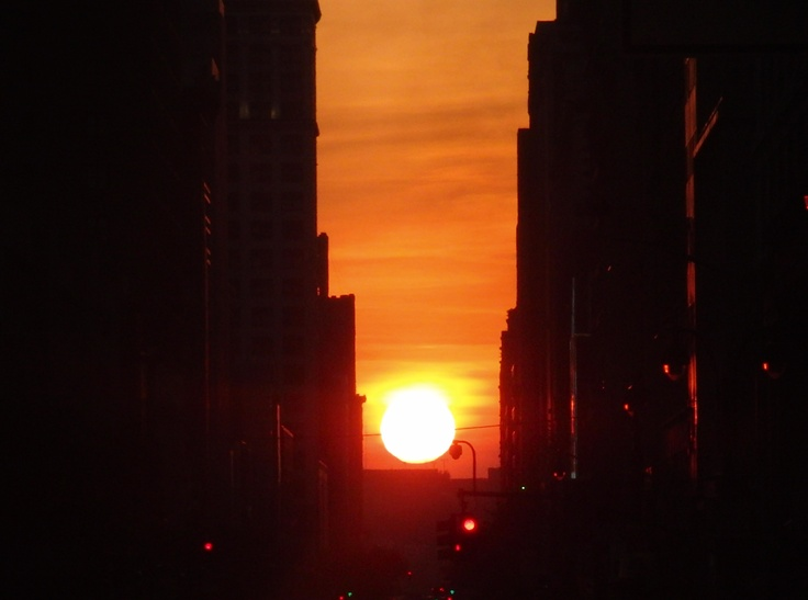 "Manhattanhenge. (photo: twi-ny/mdr) Twice a year the Sun sets between the skyscrapers of the east-west streets in what astrophysicist Neil de Grasse Tyson dubbed ""Manhattanhenge"" as the tall buildings are reminiscent of Stonehenge. If the Manhattan street grid were precisely aligned with the compass points, it would occur on the March and September solstices, but it happens in May and July. ©Mona Evans, ""Why Planets Have Seasons"" http://www.bellaonline.com/articles/art54046.asp"