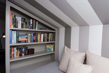 Teen kids room by Kids In Designed Spaces featuring a reading corner with custom shelves for books.