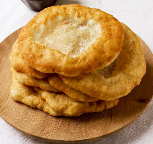 This deep fried flatbread is a common street food in Hungary, served warm with sour cream and grated cheese, rubbed with garlic or doused with garlic water.
