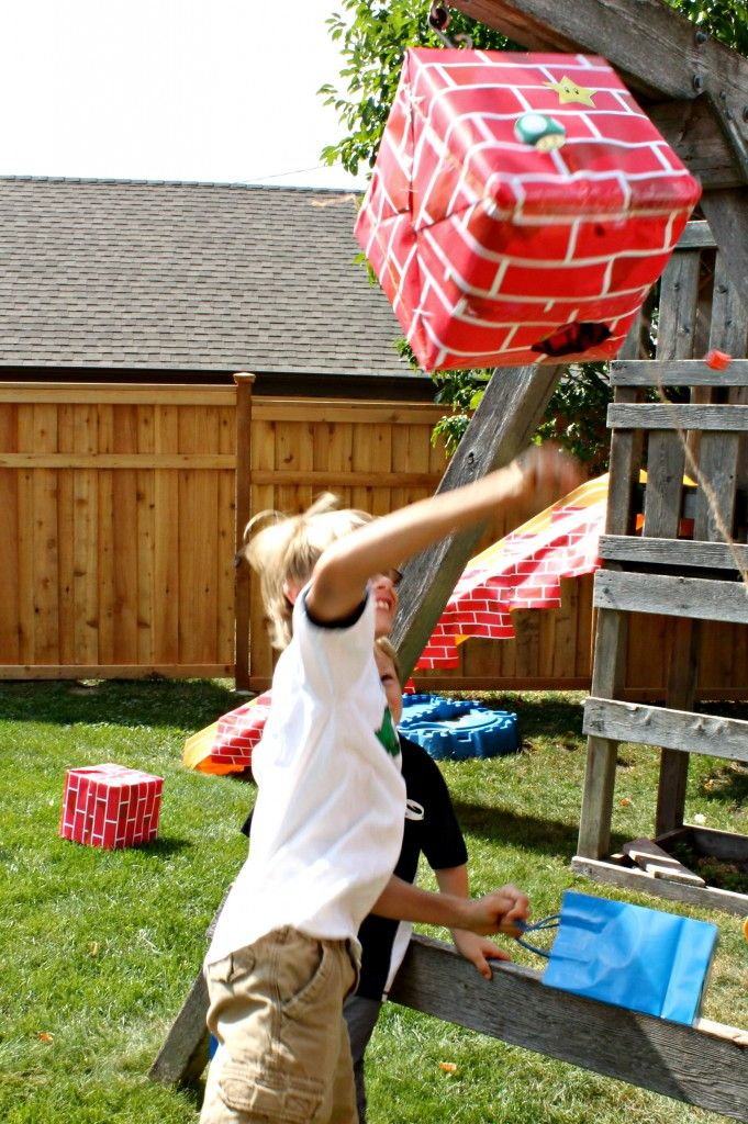 I made the pinata out of the same boxes as the blocks, with one side cut away, then wrapped in brick paper. The kids punched it like Mario w...