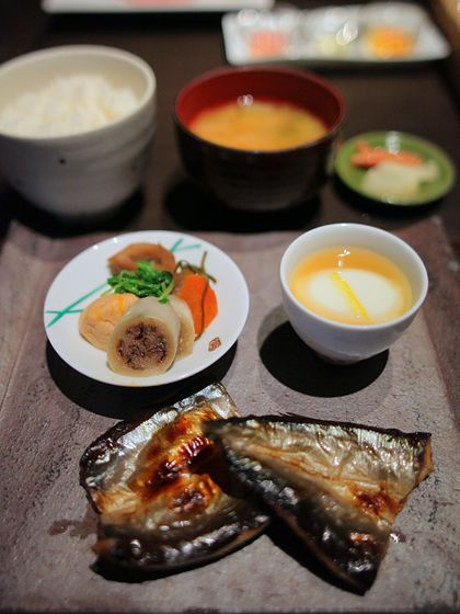 Japanese breakfast: boiled egg, grilled fish, rice, miso soup and pickles