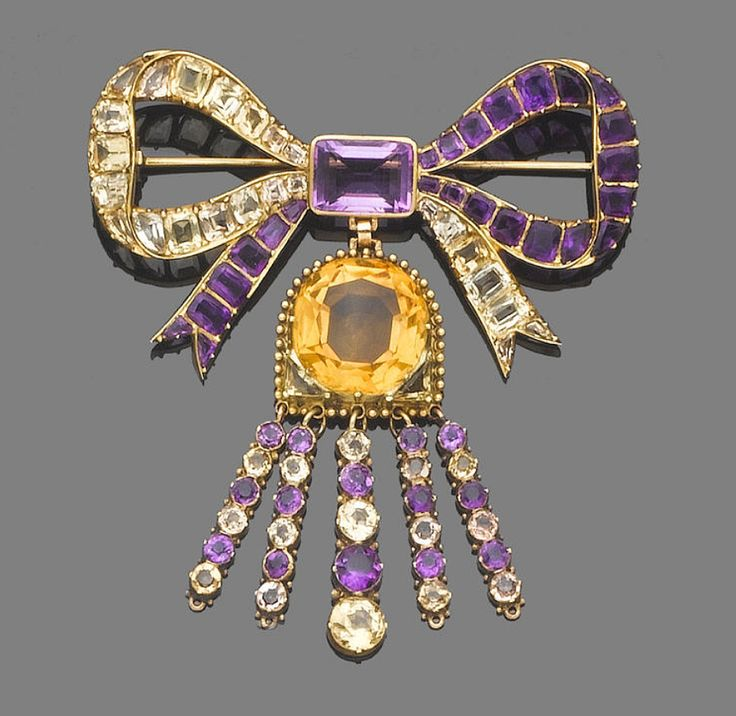 A topaz, amethyst and citrine bow brooch, circa 1900  Set throughout with step and fancy-cut amethysts and topaz, suspending an associated circular-cut citrine, terminating in a fringe of graduated similarly-cut amethysts and topaz, length 8.0cm.