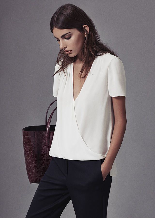 Reiss Bella Plisse-Detail Wrap Off-White Top, Joanne Cropped Tailored Trousers, and Louie Open-Top Burgundy Tote.
