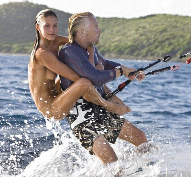 Sir Richard Branson shows off his kite-surfing moves with Denni Parkinson clinging to his back off the coast of his private Caribbean island, Necker