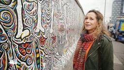 Tamina Kallert steht vor einem bemalten Stück der Berliner Mauer. | Bildquelle: wdr