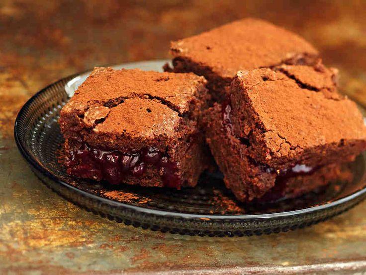 Leivo tummasta suklaasta ja hillosta. Suussa sulavat mustaherukkaleivokset koristellaan kaakaojauheella.