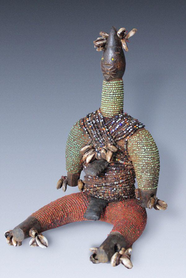 A beaded Power-Figure, doll, fertility-figure, tribe of the Namji-people, Cameroon Figur in sitzender Haltung die mit zahlreichen Kaurieschnecken geschmückt und von farbigen Glasperlensträngen umwickelt wurde. Figuren dieses Typs hatten sowohl die Steigerung der Fruchtbarkeit bei jungen Frauen als auch die Schadensabwehr zu gewährleisten, im weiteren Sinne also auch die Funktion einer Fetischfigur. Während die meisten Namchi-Puppen meist streng aufrecht -und mit hängenden Armen ausgefü...