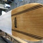 The finished product , a brand new wooden surfboard.