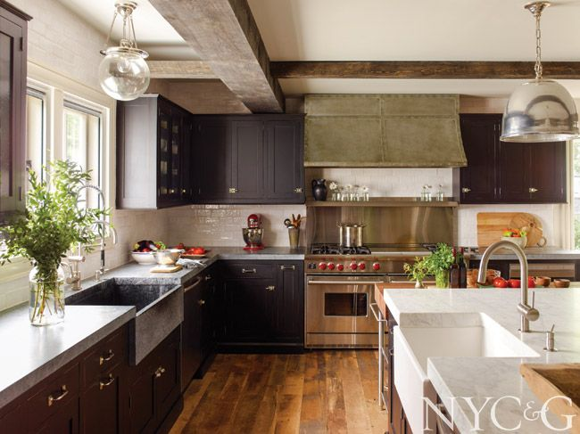 Dark cabinetry anchors bright appliances and finishes.