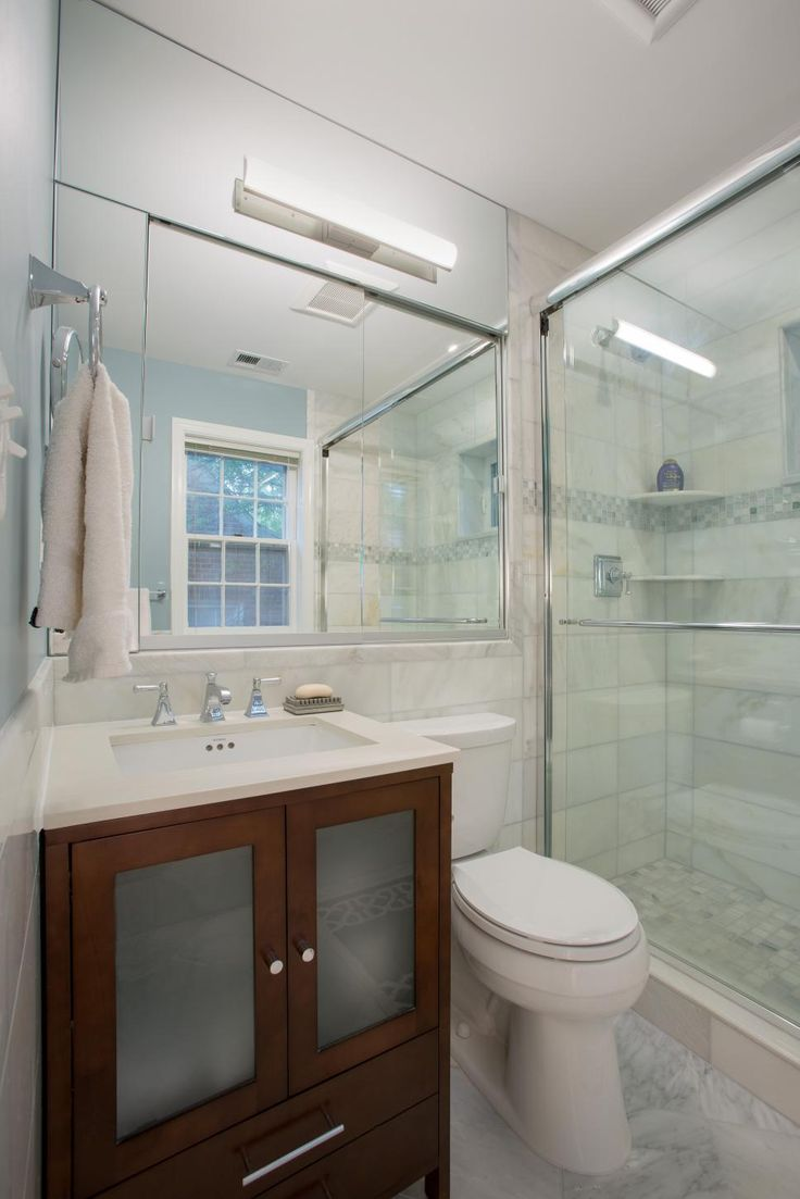 Little details give this white bathroom subtle style: a gray mosaic tile stripe in the shower, the simple wood vanity, the marble floor. Filling the wall above the sink and toilet with mirrors helps the small space feel big.