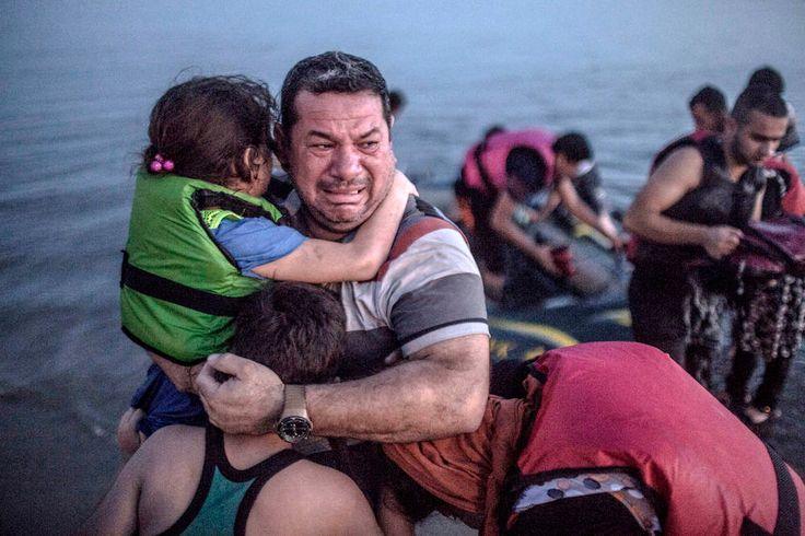 En sterkt preget flyktningefar bærer barna sine i land fra en gummibåt. Fotografi.
