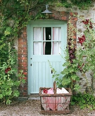 Hollyhocks by cottage door