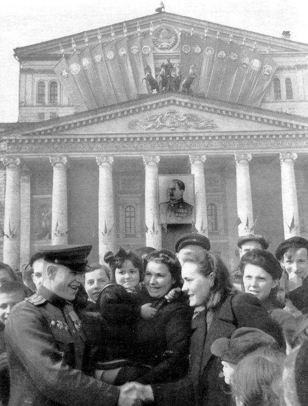 Советские граждане поздравляют офицера с Победой на фоне Большого театра в Москве. 9 мая 1945 года.