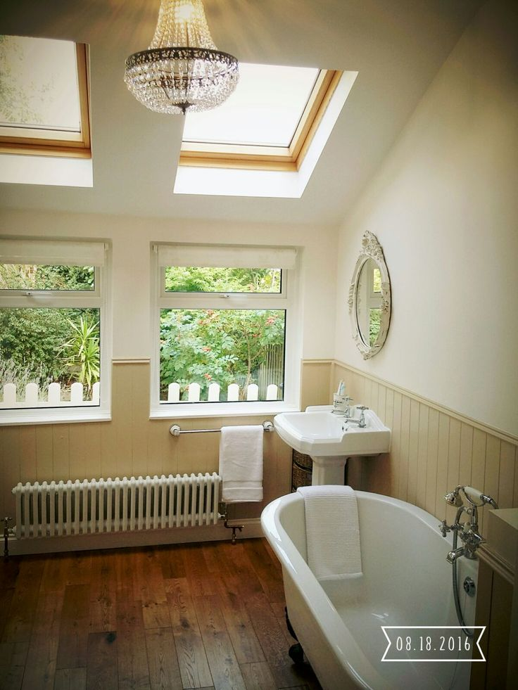 DIY bathroom project. Cambridge Claw foot tub from Bathstore. Solid oak hand stripped floor boards. Chandelier. Dunelm towel rail. Tongue and groove wall panelling painted in Stone by Homebase. Wimborne White walls by Farrow and Ball. Vintage mirror and radiator.