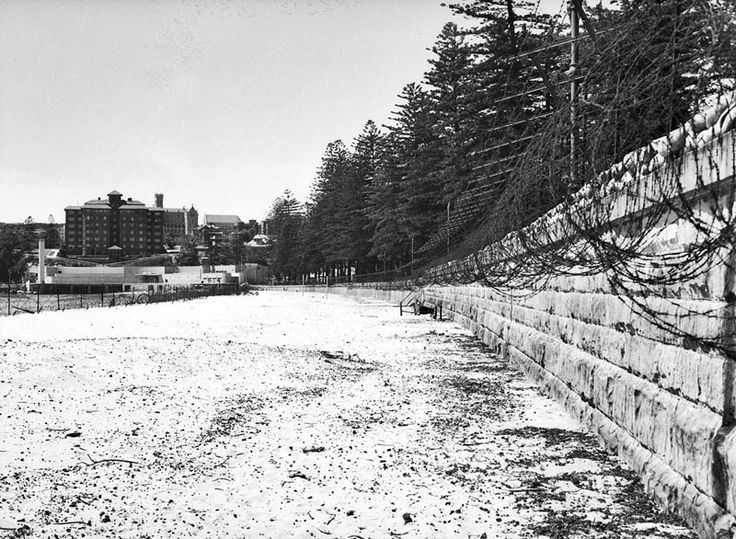 Barbed wire entanglements along Manly Beach during WW2 in Sydney, Australia. Sydney's beaches faced the threat of enemy attack during World War 2. Tank traps, bomb shelters & barbed wire fences were built along several city beaches after houses in the Eastern Suburbs were struck by shelling launched from a Japanese submarines in June 1942. v@e.