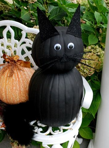 To make a black cat out of pumpkins, all you need are a tall pumpkin for the body, a smaller round pumpkin for the head (turned upside down), some black felt, black craft paint, a black boa, and some eyes. {centsationalgirl.com)