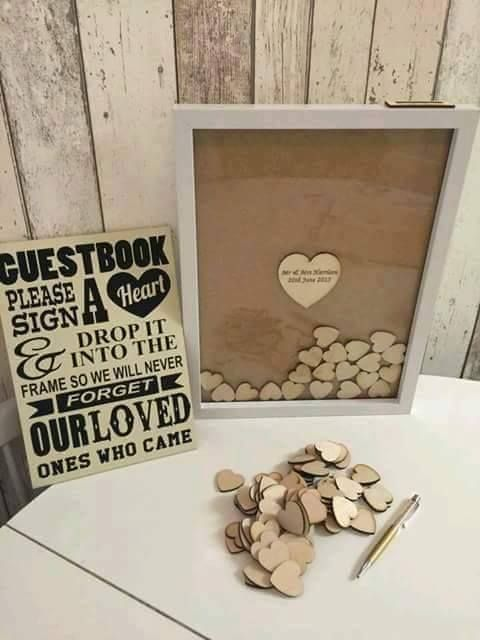 """Non-traditional """"guest book"""". Guests sign on wooden (or other material) heart shapes and drop into a picture frame."""