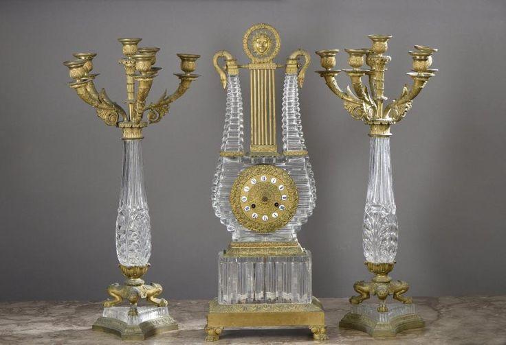 Pendule et paire de candélabre en cristal et bronze doré. Epoque Charles X. La pendule en forme de lyre en cristal sur un socle rectangulaire est ornée de cols de cygne, d'un soleil, de roses et de palmette… - Morel - 01/02/2017