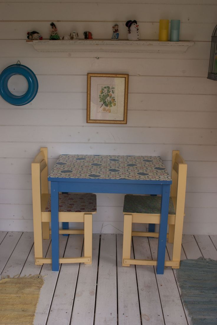 Inside of playhouse. Small blue table with wallpaper on top. Chairs in yellow and with wallpaper. See more at www.evabyeva.dk