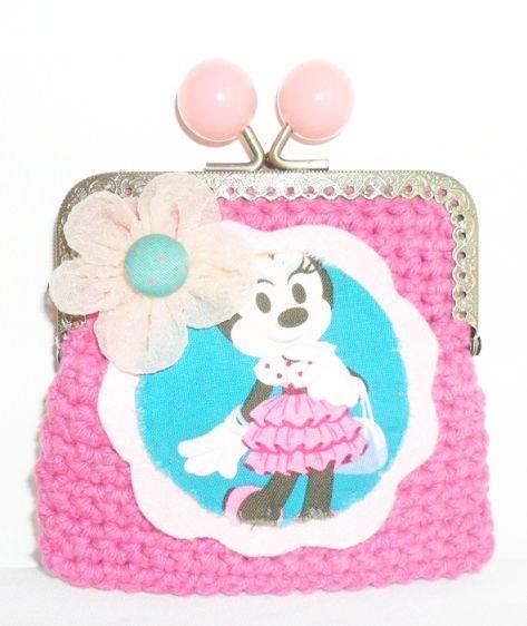 Carteira feita em linha barbante na cor rosa chock. Fecha com fecho metálico e a decorar tem uma aplicação da Minnie com uma flor em organza. Tamanho aproximado: 10cm x 12 cm Preço: 5€