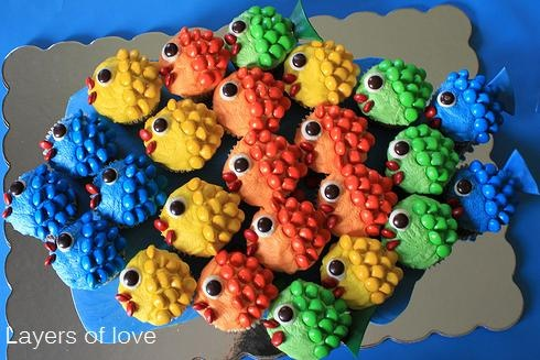 decorated fish cupcakes positioned in the  shape of a fish.