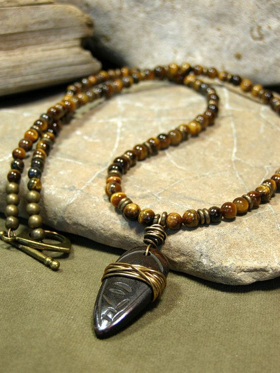 A great mens necklace beaded with 4mm tiger eye stones and Ethiopian brass heishi mixed in. A carved bone pendant that has been dyed dark brown then wire wrapped with brass wire which creates a more primitive style pendant. The classy tiger eye stones beaded together with a more primitive style pendant creates a nice combination mix of classy and rustic. Finished off with a brass toggle clasp.  Length: Choose the length you need from the drop down menu. ***This will be a custom order made to…