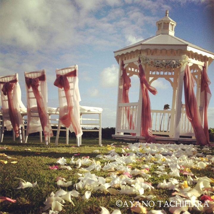 ハワイ オアフ島・カハラホテルでのウエディング。 白く可愛らしいガゼボにピンク柔らかい布を垂らし、風に優しく揺れるガーデンウエディングならではの世界観。芝生のバージンロードには、たくさんの花びらを♪
