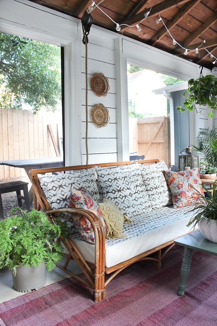 Vintage bamboo sofa in this plant-filled screened porch